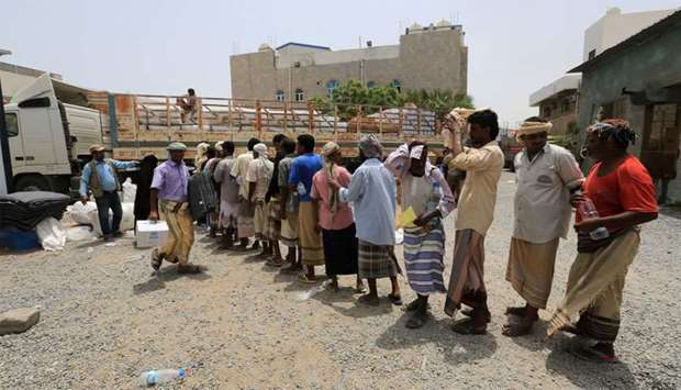 People displaced by the fighting near the Red Sea port city of Hodeidah queue to receive aid from Un