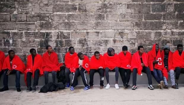 Migrants intercepted aboard two dinghies off the coast in the Strait of Gibraltar, rest after arrivi