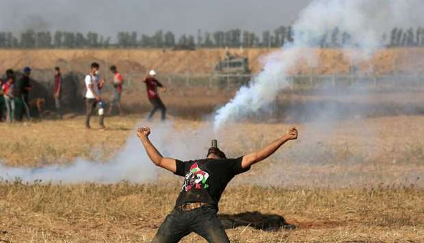A Palestinian protester holds a tear gas canister in his mouth during a demonstration along the bord
