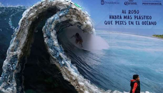 A billboard portraiting a man, surfing a wave made out of plastic bags and bottles - Santiago, Chile