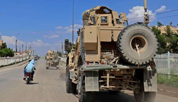 Vehicles from the US-led coalition battling the Islamic State group patrol the town of Rmelane in Sy