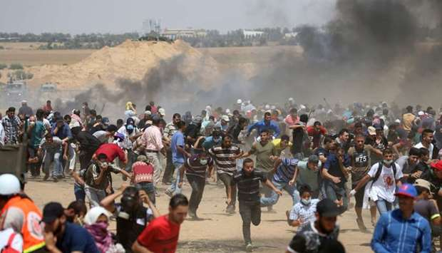 Palestinian demonstrators run for cover from Israeli gunfire during a protest marking al-Quds Day,