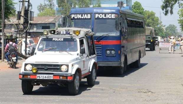 Indian Punjab Police personnel escort a police vehicle carrying the seven accused for the rape and m