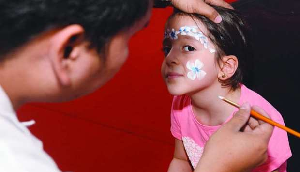 White flowers for a young girl enjoying face painting.