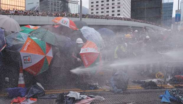 Protesters are hit by police water cannon during a demonstration against a proposed extradition bill