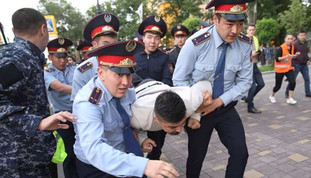 Law enforcement officers detain a man during an opposition rally held by critics of Kazakh President