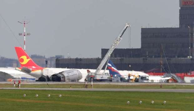 Members of emergency services operate a crane at the scene of an incident involving an Aeroflot Sukh