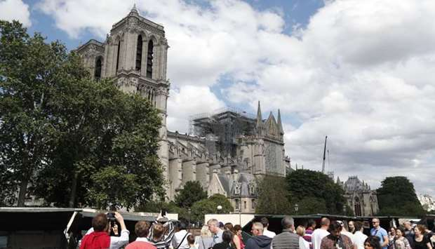 People walk along the banks of the River Seine past the Notre-Dame de Paris cathedral.