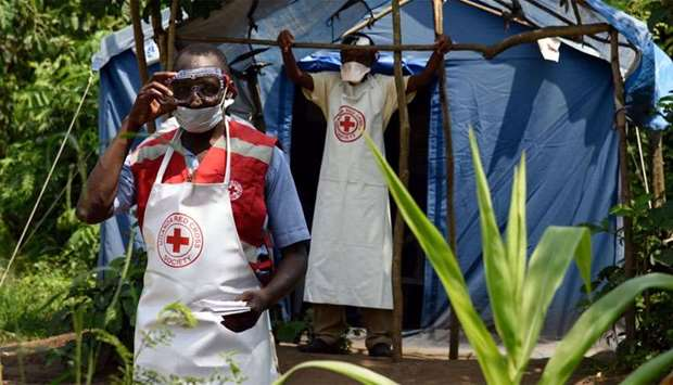 Health workers stand at a non-gazetted crossing point in the Mirami village, near the Mpondwe border