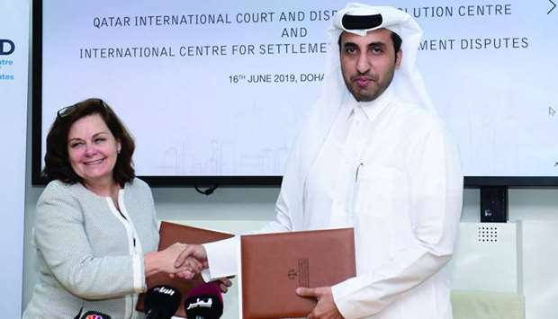Al-Sahouti and Kinnear shake hands after signing the QICDRC-ICSID agreement.