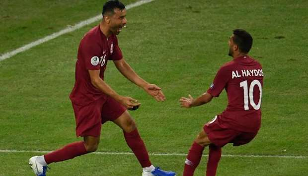 Qatar's Boualem Khoukhi (L) celebrates with teammate Hassan Al-Haydos after scoring against Paraguay