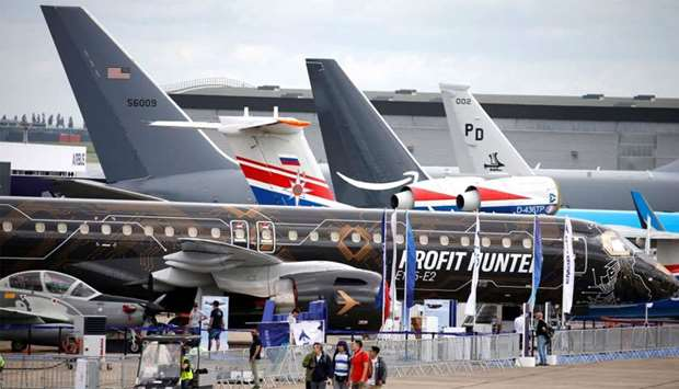 People walk past aircrafts on static display, at the eve of the opening of the 53rd International Pa