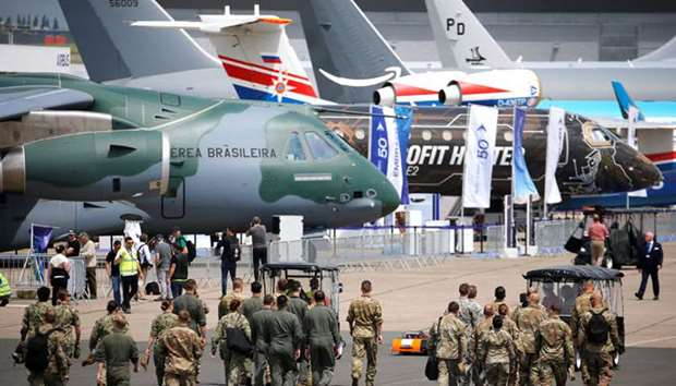 Soldiers walk past aircrafts  at the eve of the opening of the 53rd International Paris Air Show