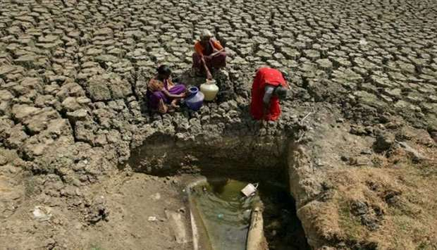 Women fetch water from an opening made by residents at a dried-up lake in India