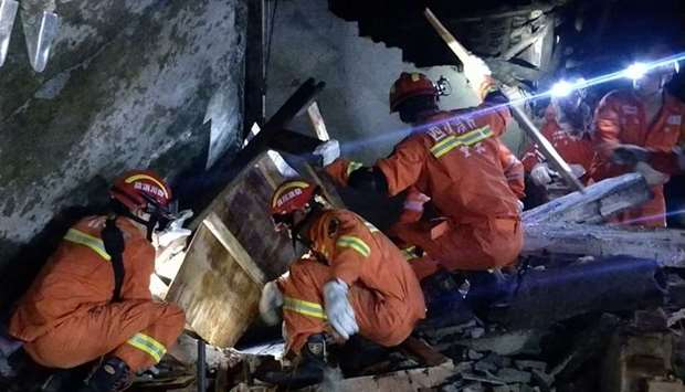 Rescuers search for earthquake survivors in the rubble of a building in Yibin, in China's southwest