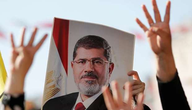 People flash Rabia signs as they hold a picture of former Egyptian president Mohamed Mursi during a