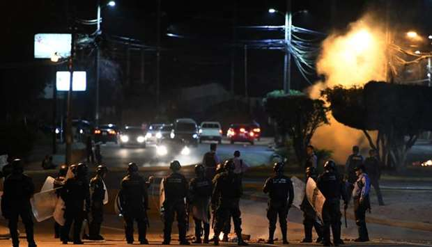 Members of the militar police release tear gas to the protestants in Tegucigalpa on June 19, 2019, d