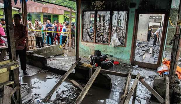Onlookers gather in front of a burnt-out house that doubled as a matchstick factory in Binjai
