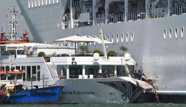 Rescuers stand onboard the damaged River Countess tourist boat after it was hit early on June 2, 201