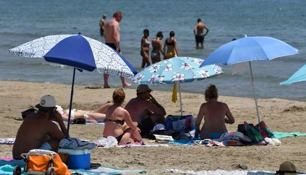 People on the beach protect themselves from the sun under umbrellas during a heat wave in Palavas-le