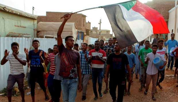 Sudanese protesters chant slogans and wave their national flag as they demonstrate against the rulin