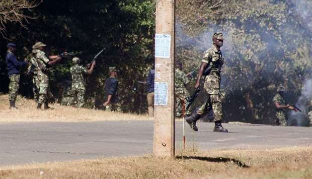 Armed Malawian policemen walk through a cloud of teargas as they disperse supporters of The Malawi C