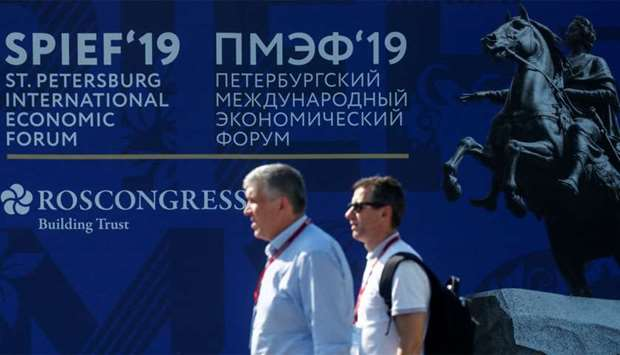 Participants walk next to the logo of the St Petersburg International Economic Forum (SPIEF) in St P