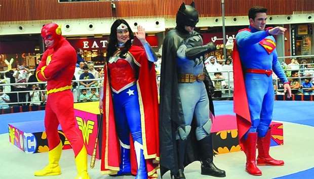 (From left) The Flash, Wonder Woman, Batman, and Superman wave to young fans during a live show at t