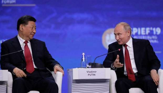 Russian President Vladimir Putin and Chinese President Xi Jinping attend a session of the St. Peters