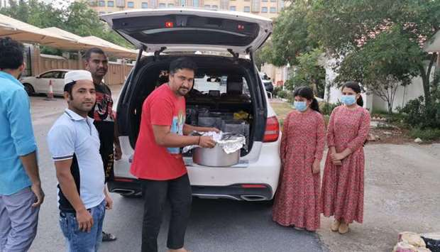 FOOD DISTRIBUTION: From right, Rawda seen with her sister and house staff while loading food to be d