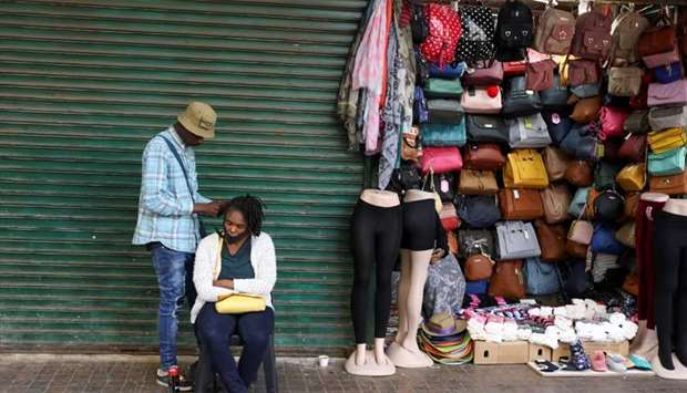 A roadside hairdresser attends to a customer, openly flouting lockdown regulations amid the spread o