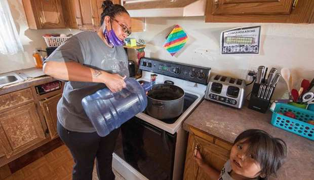 Amanda Larson who has no running water at her home, carries water for her son Gary Jr to have a bath