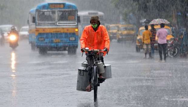 A milk vendor wearing a protective face mask rides his bicycle during heavy rain, after authorities