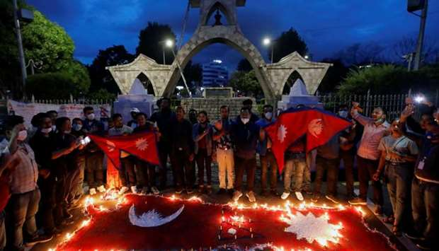 Nepalese people light candles as they celebrate after the parliament approved a new map of the count