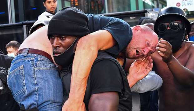 A protester carries an injured counter-protester to safety, near the Waterloo station during a Black
