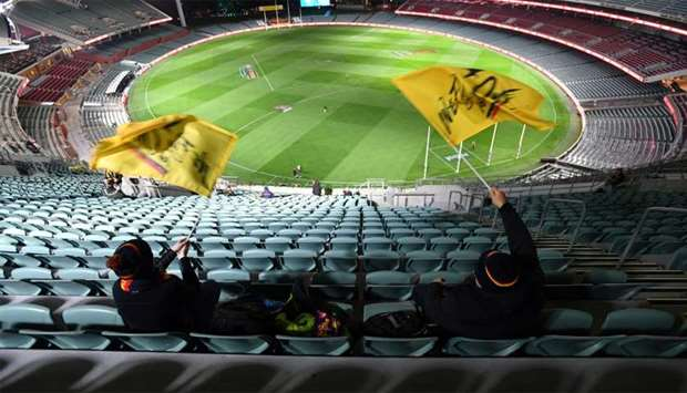 Fans wave flags before an Australian Football League (AFL) match between the Port Adelaide Power and