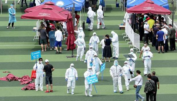 Medical workers in protective suits help people lining up inside a sports centre for nucleic acid te