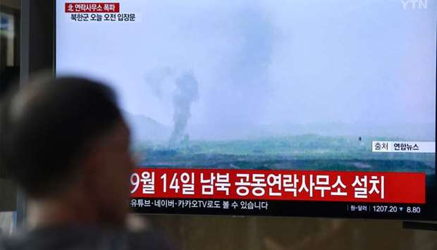 People watch a television news screen showing an explosion of an inter-Korean liaison office in Nort
