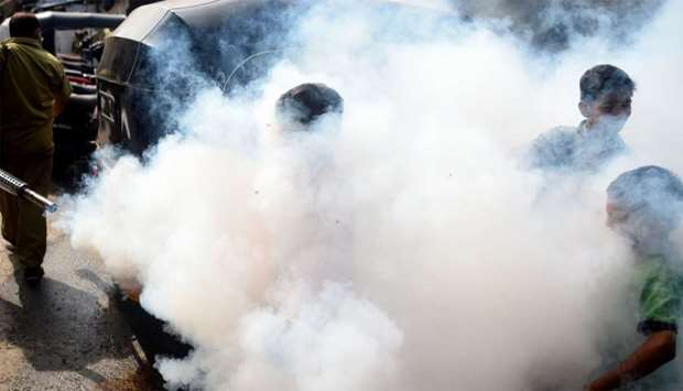Children are covered in smoke as a civic authority worker (L) fumigates an area to kill disease-carr