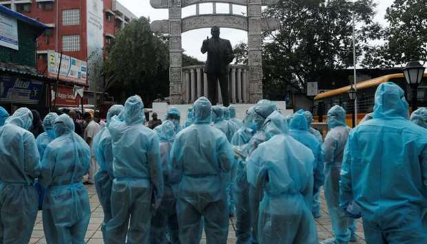 Healthcare workers stand in front of a statue of Babasaheb Ambedkar, founder of the Indian Constitut