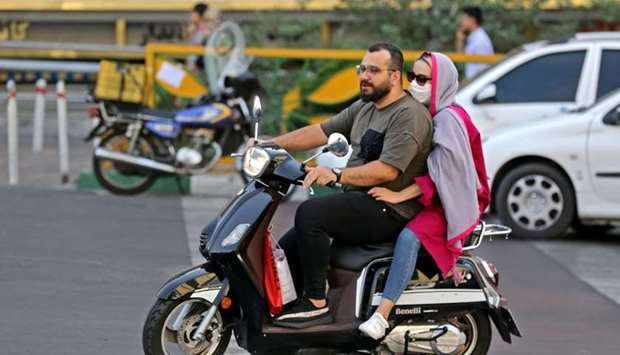 An Iranian woman wearing a face mask rides on the back of a motorcycle in Tehran