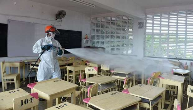A health worker sprays disinfectant in a classroom at the Anula school, in the suburb of Nugegoda in