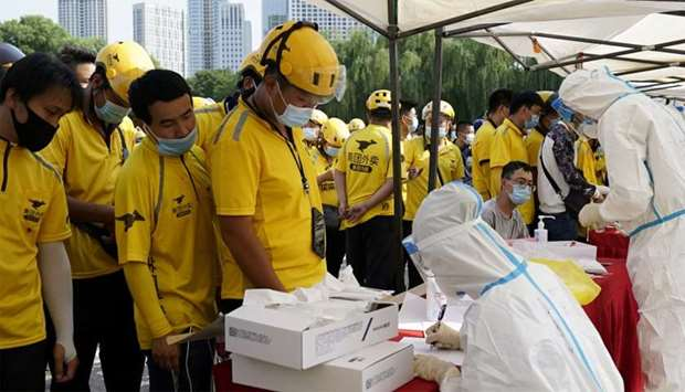 Meituan delivery workers wearing face masks wait in line to take nucleic acid tests, following a new