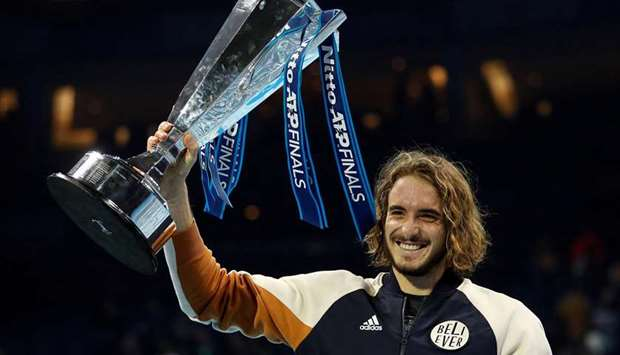 Greece's Stefanos Tsitsipas celebrates winning the ATP Finals with the trophy in London on November