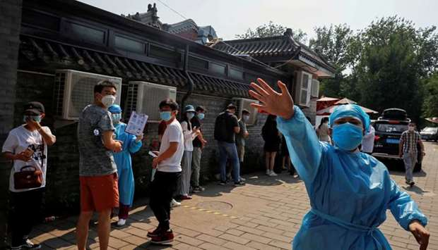 A nurse in a personal protective equipment (PPE) gestures at the photographer outside a makeshift te