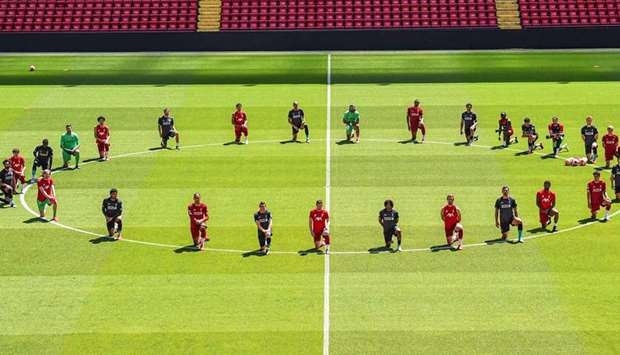 Liverpool players take a knee around the centre circle at Anfield yesterday. (Twitter/LFC)