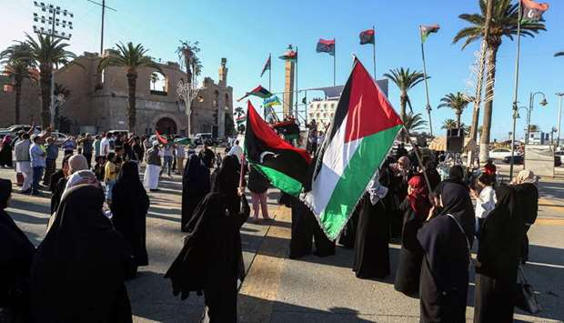 Women and children wave flags of Libya and Palestine in the Martyrs' Square in the centre of the Lib