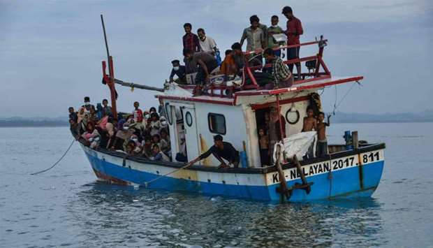 A boat carryingg Rohingya people from Myanmar arrives on the shorelines of Lancok village, in Indone