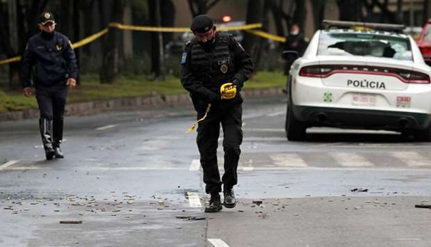 A police officer walks amid ammunition near the scene of a shooting in Mexico City, Mexico