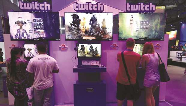 Visitors stream online computer games on the Twitch Interactive stand at Gamescom video games trade